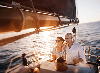 Couple stands on a sail boat out on the water