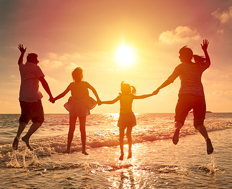 image of family on the beach at sunset